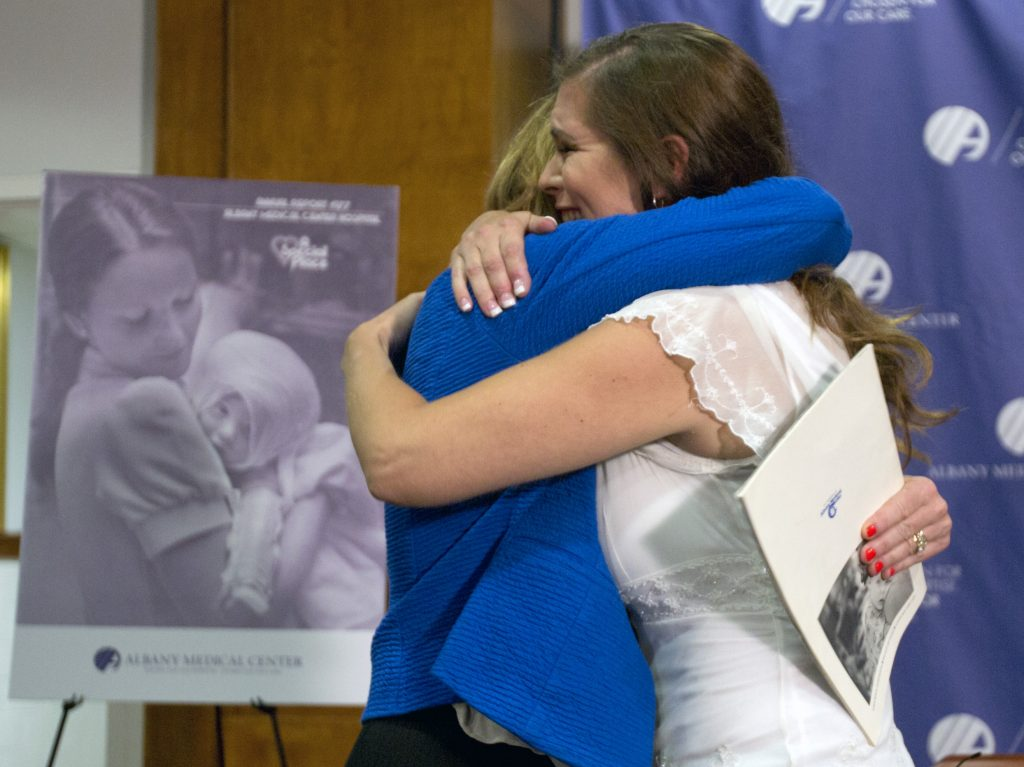 Nurse Susan Berger, left, and Amanda Scarpinati hug during a news conference at Albany Medical Center, Tuesday, Sept. 29, 2015, in Albany, N.Y. Scarpinati, who suffered severe burns as an infant, is finally getting the chance to thank Berger who cared for her, thanks to a social media posting that revealed the identity of the nurse in 38-year-old photos. (AP Photo/Mike Groll)