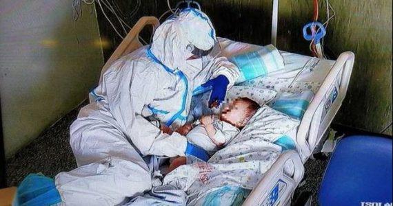 Un'infermiera accarezza un neonato ricoverato con il Covid, la foto fa il giro del web